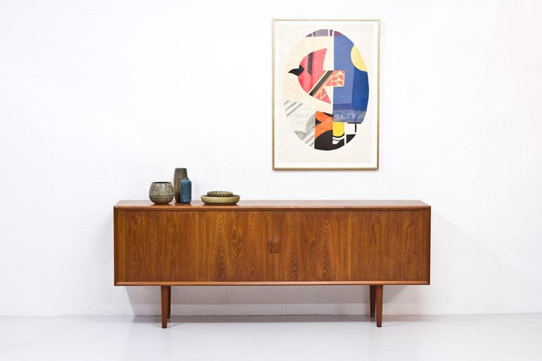 Sideboard designed by Svend Aage Larsen. Manufactured in Denmark by Faarup Mobelfabrik during the 1960s. Made from teak with tambour doors. Inside with drawers and shelves.