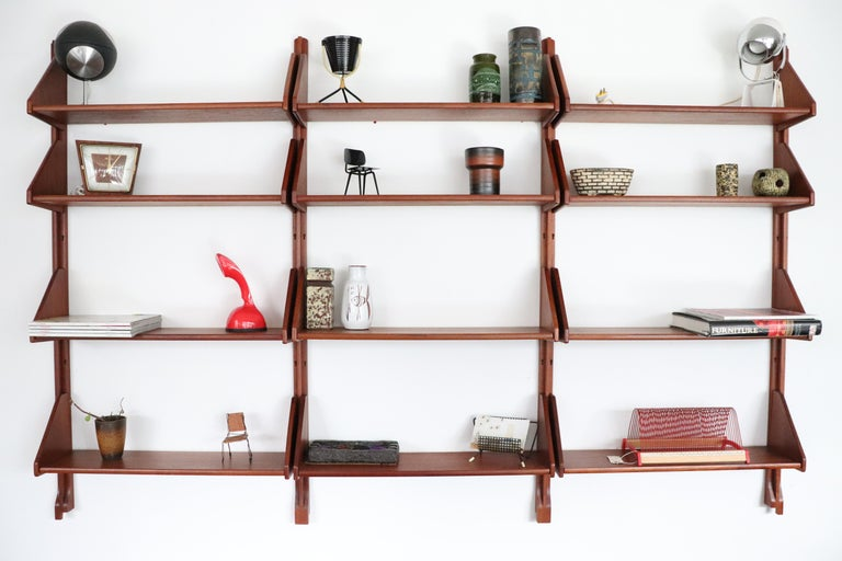Handsome Danish teak wall mount shelving unit with all wood risers and shelves. Very nice original condition. Accessories, as pictured, not included.