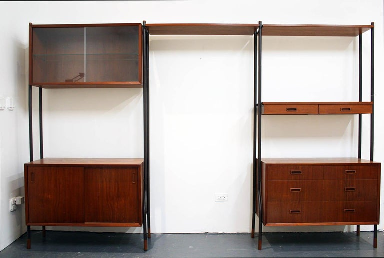 A beautiful freestanding design made in Denmark. This gorgeous unit features all very well kept teak wood cabinets and shelves. It includes a 3 drawer box, a teak box with an interior glass shelf and 2 glass sliding doors, a 2 drawer teak shelf and