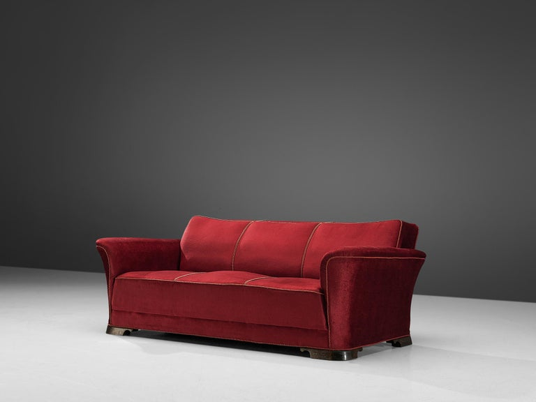 Three-seat sofa, velours and mahogany, Denmark, 1940s  A grand and comfortable three-seat sofa in red velours upholstery. The sofa features a thick seat, which is characteristic for the Art Deco movement. Large upsweeping armrests curve slightly