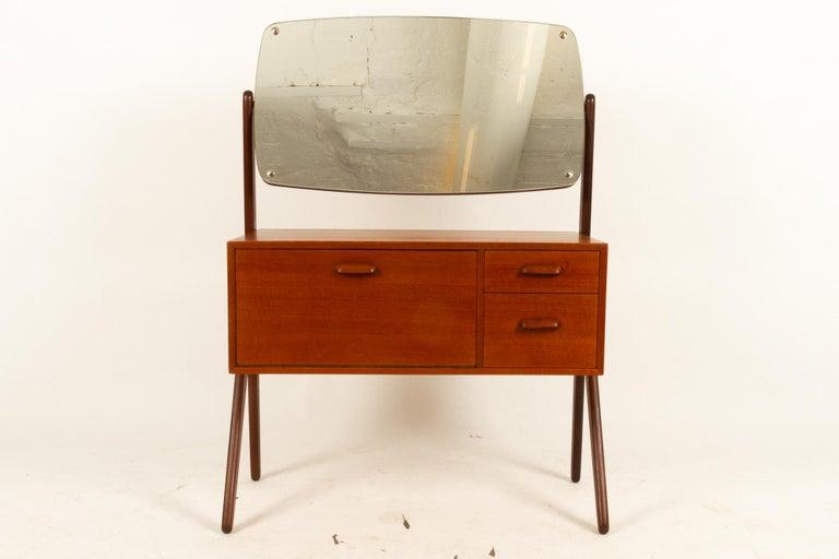 Danish vintage teak vanity by Ølholm 1960s Elegant Mid-Century Modern dressing table in teak with large mirror. Features cabinet and two drawers. Mirror can be tilted. Y-legs in solid teak. Height tabletop: 60 cm / 24