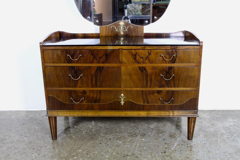 Danish vanity with 2 matching bedside tables. The vanity has a large foldable 3-winged mirror and an elegant black glass top with engraved motifs. 3 large drawers that runs incredibly smooth. Beautiful walnut veneer. Nightstands has matching glass