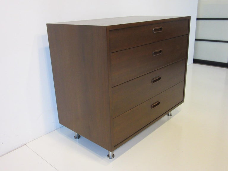 A dark walnut smaller sized four-drawer dresser chest with matching pulls sitting on brushed stainless steel adjustable legs, the backside is finished in the same walnut designed by Poul Cadovius for Cado with replaced legs.