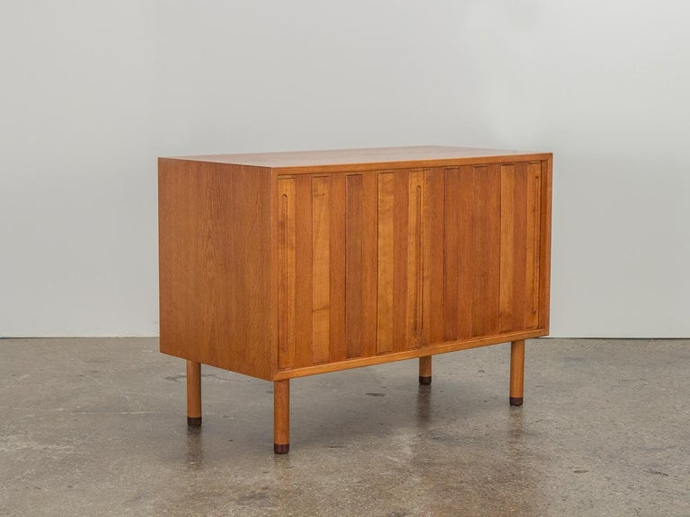 Seldom seen in this compact form, Danish white oak sliding door cabinet designed by Hans Wegner for Ry Møbler. This high-quality case piece has very interesting design details, including round feet capped with rosewood. Hand-pulls are inset at the