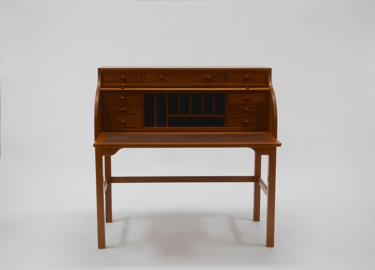 Andreas Hansen roll top teak desk, manufactured by Form75 in Hadsten, Denmark. Featuring a locking tambour roll top concealing a fitted superstructure and a pullout / pull-out leather writing surface.   Measures: 44