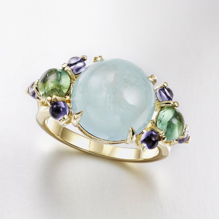 A luxurious cocktail ring in 18 karat yellow gold featuring a claw set 12mm round aquamarine center stone, with prong set green tourmaline and iolite gems on both sides of the stone to complement.  This ring can be sized to fit your finger. Please