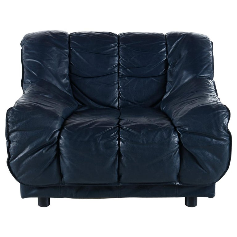 This luxurious Italian leather armchair challenges the eye. It does appear to be black, but in the right light one can notice a slight blue tint. The chair sits like a dream with the amply stuffed cushions cradling the body like a cuddly cloud. The