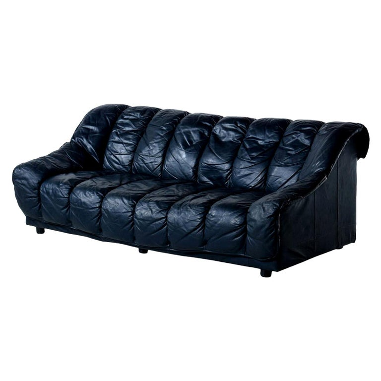 This luxurious Italian leather armchair challenges the eye. It does appear to be black, but in the right light one can notice that the leather is actually a deep blue color. The chair sits like a dream with the amply stuffed cushions cradling the
