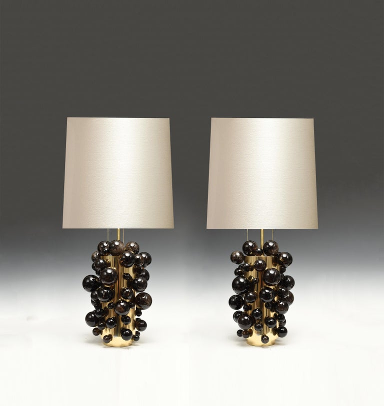 A pair of luxury dark rock crystal quartz bulb lamps with polish brass frame. Created by Phoenix Gallery, NYC. Each lamp installed two sockets. To the top of the rock crystal 17 inch. Lampshade not included.