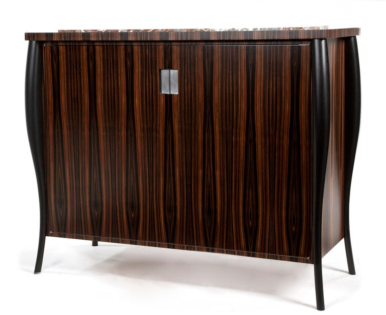 Book-matched Macassar ebony drinks cabinet.  The hand-sculpted legs in ebonised walnut and waterfall veneer edging encase a beautiful Irish stone top.   The interior of the cabinet is made from ripple sycamore and the inset handles are finished