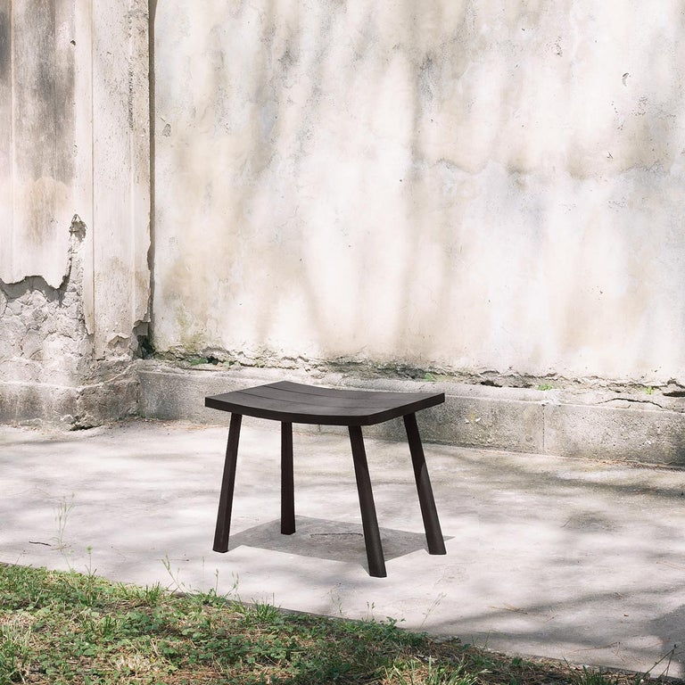 This low bench is 47 cm high and made entirely in solid, dark oakwood. Available in brown, it features a concave seat, without armrests or back. Suitable for indoor or outdoor use, the item can also be ordered in solid Canaletto walnut or solid