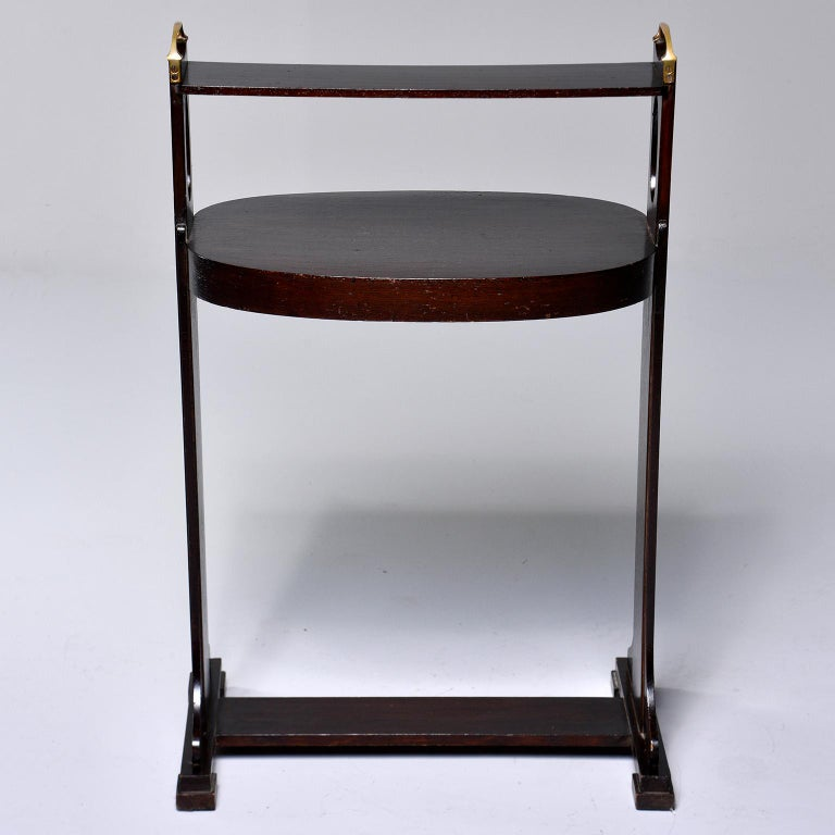 Arts & Crafts dark stained palisander stand or side table, circa 1920s. Footed base with decorative cutout in side supports, oval tabletop and narrow top rail with brass handles. Unknown maker. Found in England.