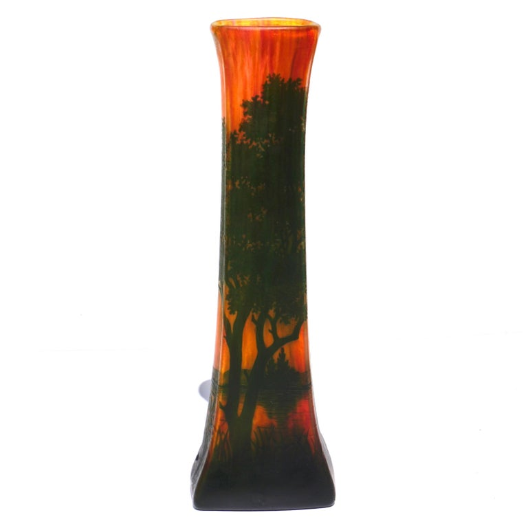 A warm scenic tall vase by Daum Freres from Nancy France circa 1900. The scene is a landscape with lake and green trees and bushes in the fore and back ground. The interesting feature of this four sided tapered vase in the yellow, orange and red