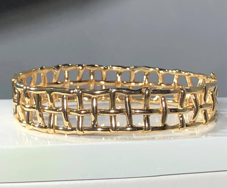 Daunis 14 karat yellow gold hinged cuff bracelet. This piece is a Daunis creation. Created in 14 karat yellow gold weighing 34.1 grams and 21.8 dwt. Gate/stake closure with safety clasp. Such a Modern twist on a classic staple piece. This cuff