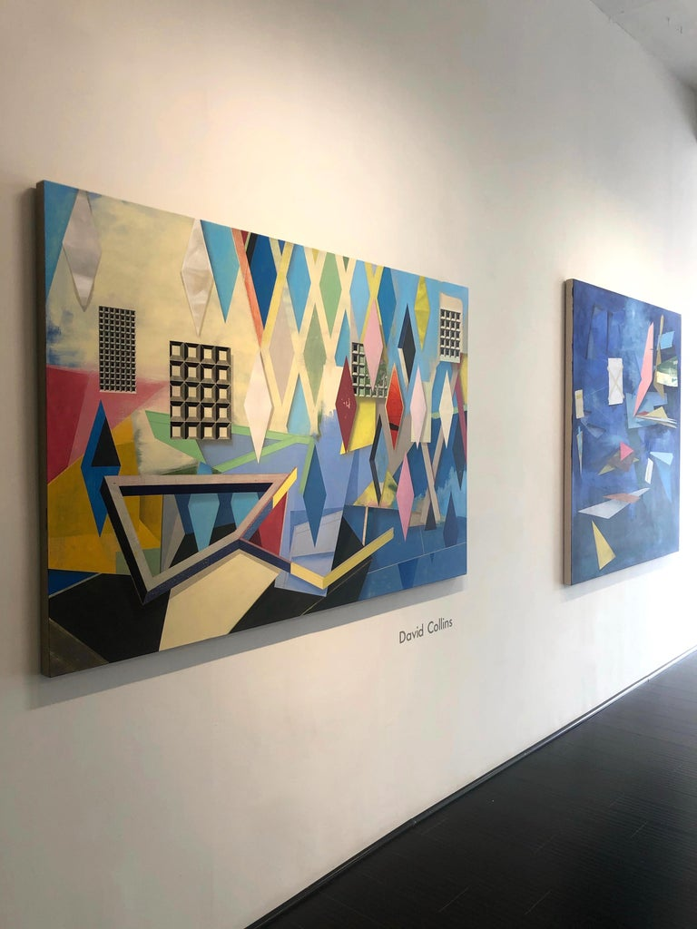 For Nothing is Fixed is a large horizontal geometric abstract acrylic painting on linen by David Collins. The blue background beautifully offsets hard-edge geometric shapes in vibrant shades of cobalt, bright blue, orange, dark pink, yellow, light
