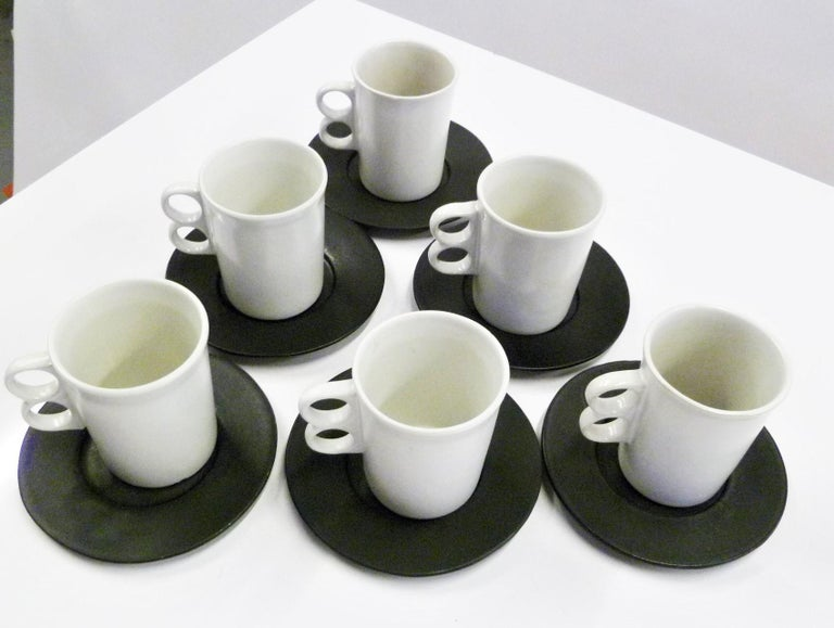 Designed by David Gil (1922-2002) for his company Bennington Potters of Vermont, a set of 6 matte white trigger mugs #1340 and 6 matte black plates/saucers. These are handmade stoneware pieces from the 1960s, each will be an individual creation thus