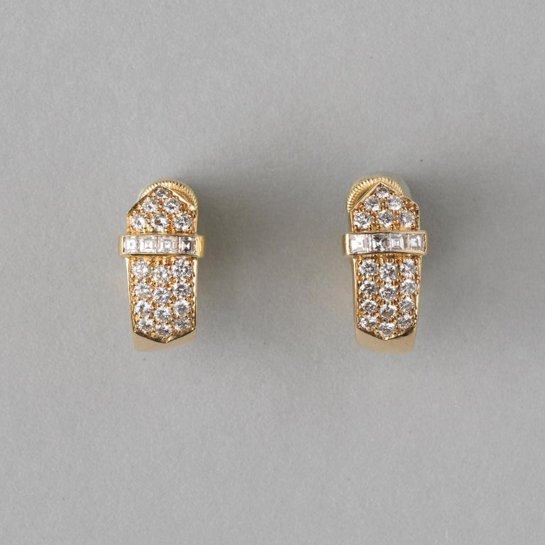 A pair of 18 carat yellow gold buckle ear clips set with brilliant cut diamonds and a little band with four carré cut diamonds  (app. 1.36 carat in total) master mark: DM for David Morris, England, 1990.  weight: 8.75 gram dimensions: 1.8 x 0.9 cm