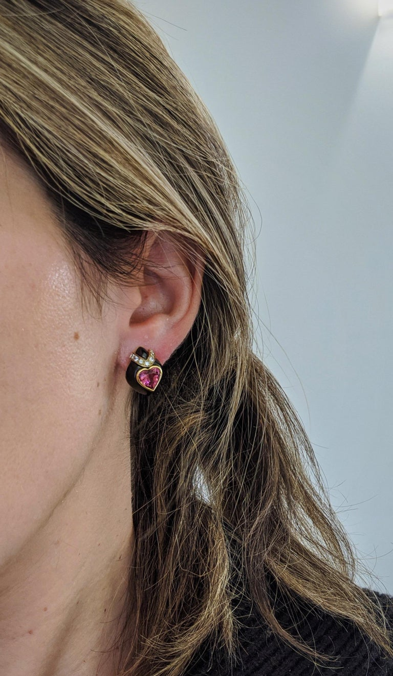 These 18 karat yellow gold teardrop shaped earrings were designed by David Morris.They feature Pink Tourmaline heart centers with a yellow gold bezel setting. The hearts sit on top of an 18 karat blackened gold setting that has been trimmed with