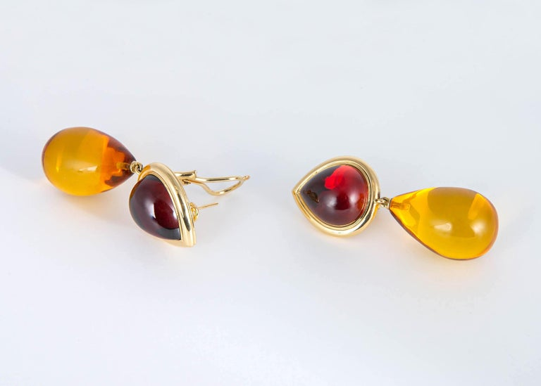 Completely handmade and unique. Featuring a pair of cabochon garnets that simply glow from with in and a rich pair of amber drops. A  true statement piece. 2 1/8 inches in length.