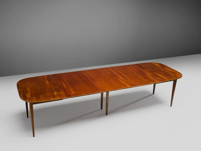 David Rosén for Nordiska Kompaniet,extremely wide extendable dining table, mahogany, Sweden, 1950s  This extendable dining table is highly elegant, due to the thin top and smoothly tapered legs. The rectangular shape has rounded corners and a