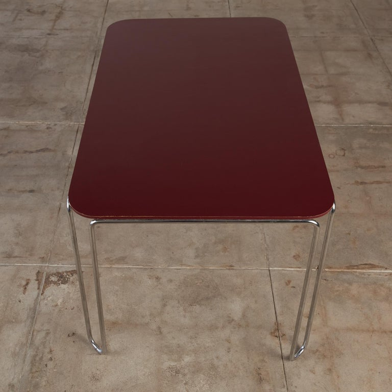 A dining table by David Rowland for GF Furniture Systems, c.1990. The Model 710 table has a burgundy laminated top that sits on top of chrome plated steel base that runs along the side of the tabletop with wire/hairpin legs. This table could also be