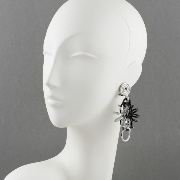Elegant David Spada, New York signed dangling clip-on earrings. Featuring a cool Space Age 1980s design with dangle articulated spirally coiled elements along with assorted size rings. Anodized aluminum metal with classy colors (black and silver).