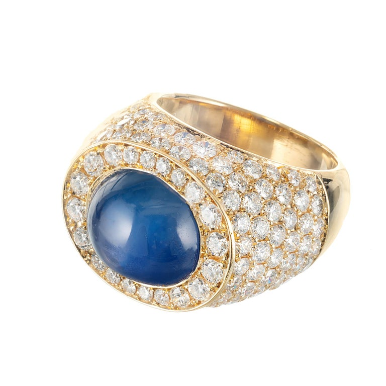David Webb Mid-Century sapphire and diamond cocktail ring. 18k yellow gold setting, accented with 134 Ideal cut sparkly diamonds around a 14.4 ct oval sapphire  center stone.   1 violet blue cabochon star sapphire, Approximate 14.4cts GIA