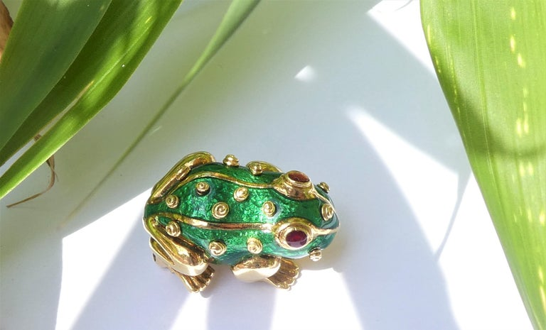 Frog Brooch of the 1970s by David Webb. It is crafted in 18 karat yellow gold with green enamel. The eyes are in red enamel. The brooch is stamped Webb and 18 karat. There are two more stamps: the letters C and R. I particularly like the 14 little