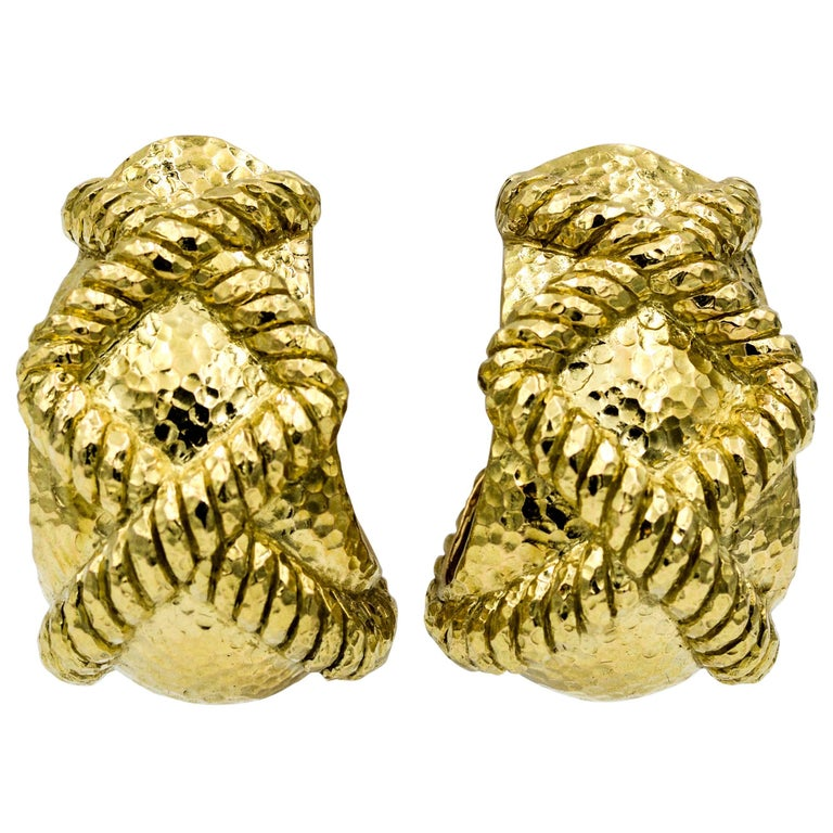 Driven by art, design and bold pieces these earrings embody David Webb's textured gold statements. These clipped back 18K yellow gold earrings have two banded X's set in a hammered finish. The earrings measure 35.25 mm tall and 22.55 mm wide, and
