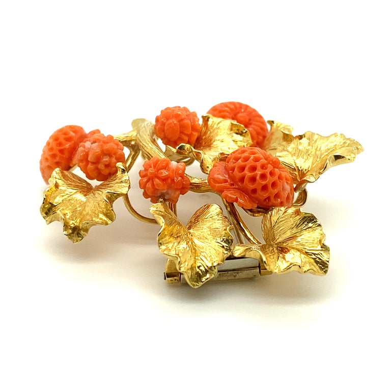 A vintage David Webb 18k gold and carved coral brooch featuring coral carved in exacting detail by hand into budding and blooming flowers, with gold leaves textured to resemble living, three-dimensional leaves.  Stamped David Webb, Webb, 18k.