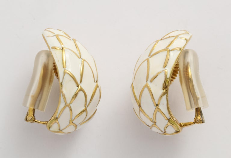 Classic David Webb ear clip is made with white enamel over 18K yellow gold. This ear clip has good volume and size, and the neutral palette is great year-round.  It's an ideal earring to travel with; great for your resort wear or your business