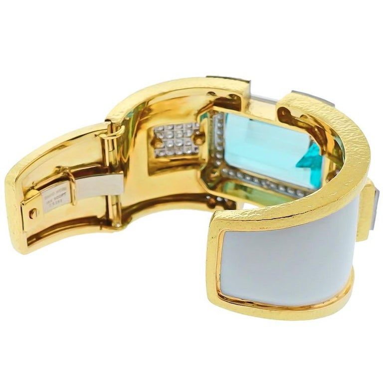 Absolutely stunning large aquamarine and diamond bangle cuff bracelet by David Webb.   Crafted in 18K Yellow gold and platinum this bracelet features a 90-carat aquamarine, enclosed in a diamond pave set halo.   Applied with white enamel, secured by