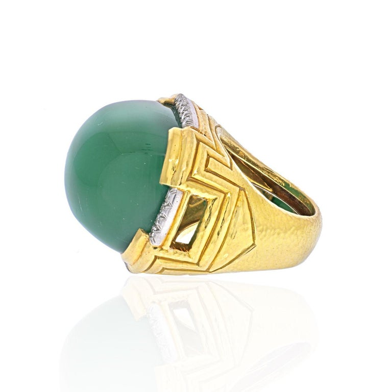 Large Green Chalcedony and Diamond Ring by David Webb. It is crafted out of solid 18K Yellow Gold with Platinum accents with a hammered finish. Showcasing one (1) cabochon cut Green Chalcedony, measuring 23.00 x 26.00 mm. Accenting the ring are