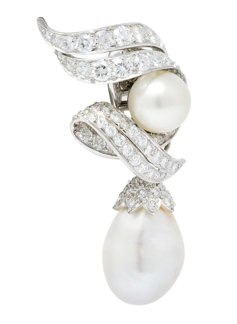Each features a 10 mm round white pearl with good luster and very pale pink overtones  Numerous bead set round brilliant diamonds surround the central pearl and adorn the bale of the drop  Platinum setting features stylized and dimensional scrolls,