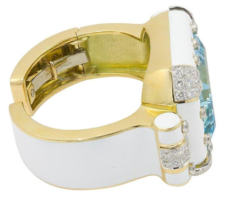DAVID WEBB Aquamarine, Diamond White Enamel Bracelet.  An 18k yellow gold and platinum bangle-bracelet, set with emerald-cut aquamarine and round brilliant-cut diamonds, signed David Webb and numbered. Inner-circumference is approx. 5.5″