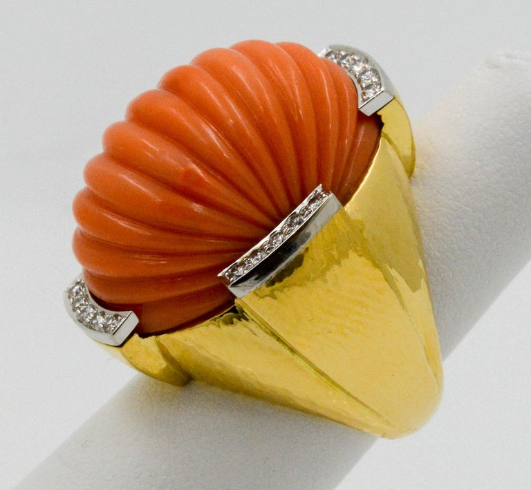 This 18k platinum and yellow gold David Webb carved coral ring is a knock out piece. It features round diamond accents with a combined total weight of .50 carats surrounding the domed coral center.