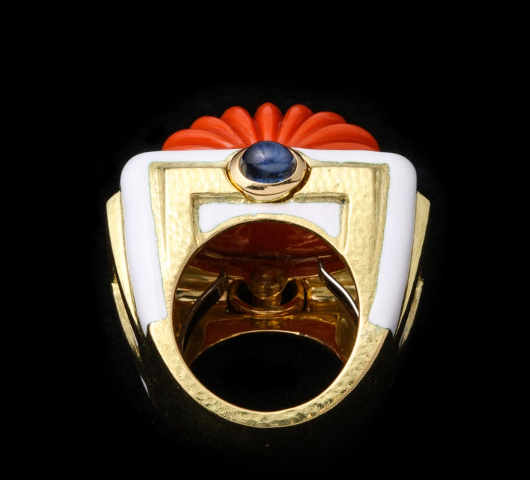 David Webb Carved Coral Ring   Set with a carved coral, cabochon sapphire, white enamel on 18 karat gold  Signed David Webb. With certificate of authenticity