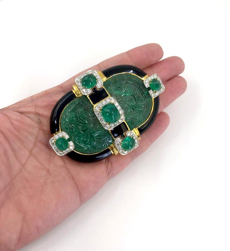 DAVID WEBB Carved Emerald Convertible Pendant Brooch in 18k Gold and Platinum.  A convertible pendant and brooch dating from the 1980s by David Webb featuring emeralds, diamonds, black enamel, and mixed metals. The look is exemplary of the decade,