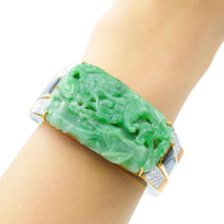 David Webb Carved Jade, Black Enamel and Diamond Cuff Bangle Bracelet In 18k yellow gold and platinum. This tapered hammered gold bangle centering a modified rectangular carved jade panel depicting a phoenix within bamboo measures approximately 52.0