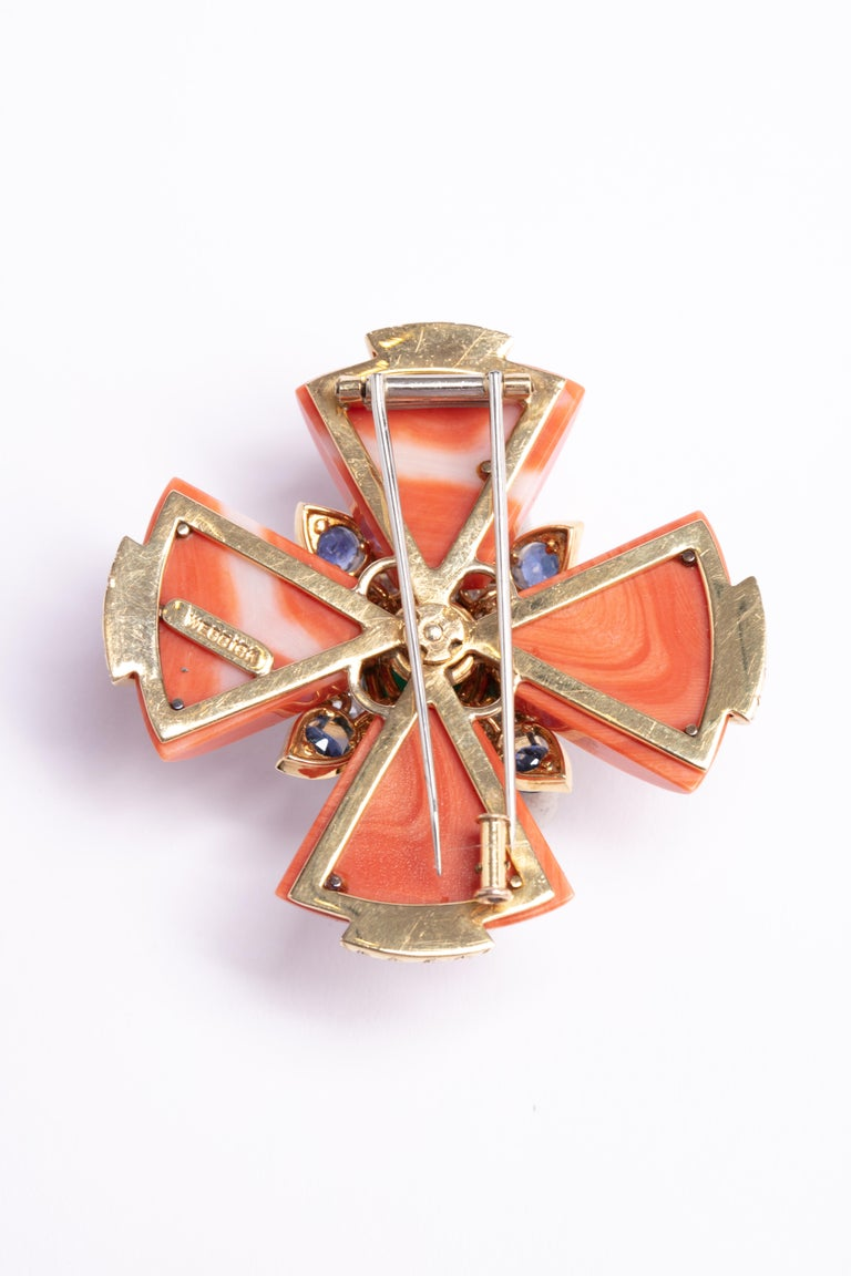 Iconic David Webb coral Maltese cross pendant with diamonds and sapphires surrounding a gorgeous emerald in the center of this show stopping pendant / brooch. 4 individual pieces of coral with 4 well colored sapphires and 84 diamonds surrounding the
