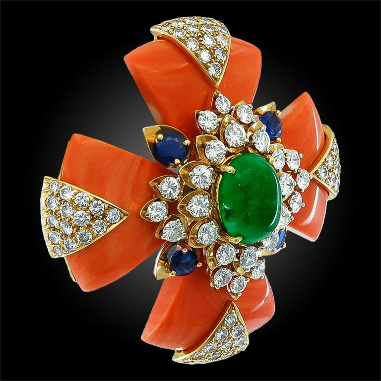An exceptional maltese cross brooch crafted by David Webb circa 1965, designed with geometric shapes comprised of coral, cabochon emerald, sapphires and brilliant diamonds mounted in 18k yellow gold.