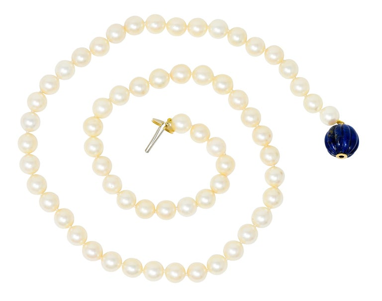 Hand knotted strand necklace comprised of round cultured pearls measuring from 8.5 to 8.8 mm  Incredibly well-matched cream body color with moderate rosè overtones and a very good luster  Terminating as a deeply fluted 14.8 mm lapis bead, opaque and