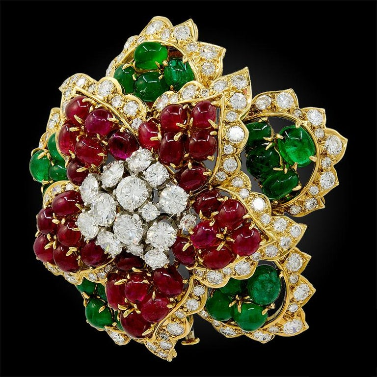 DAVID WEBB Diamond Cabochon Ruby, Emerald Brooch.  An 18k yellow gold flower brooch, set with brilliant-cut diamonds, cabochon ruby, and emerald, signed David Webb, circa the 1980s. Dimensions approx. 2.06″ in length by 1.0″ in width