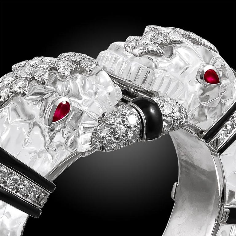 Exquisitely designed as two opposing carved rock crystal and black enamel chimera heads on an 18k gold and platinum bangle, each head detailed with pear shaped ruby eyes and round brilliant cut diamond crowns, both grasping a similarly cut diamond