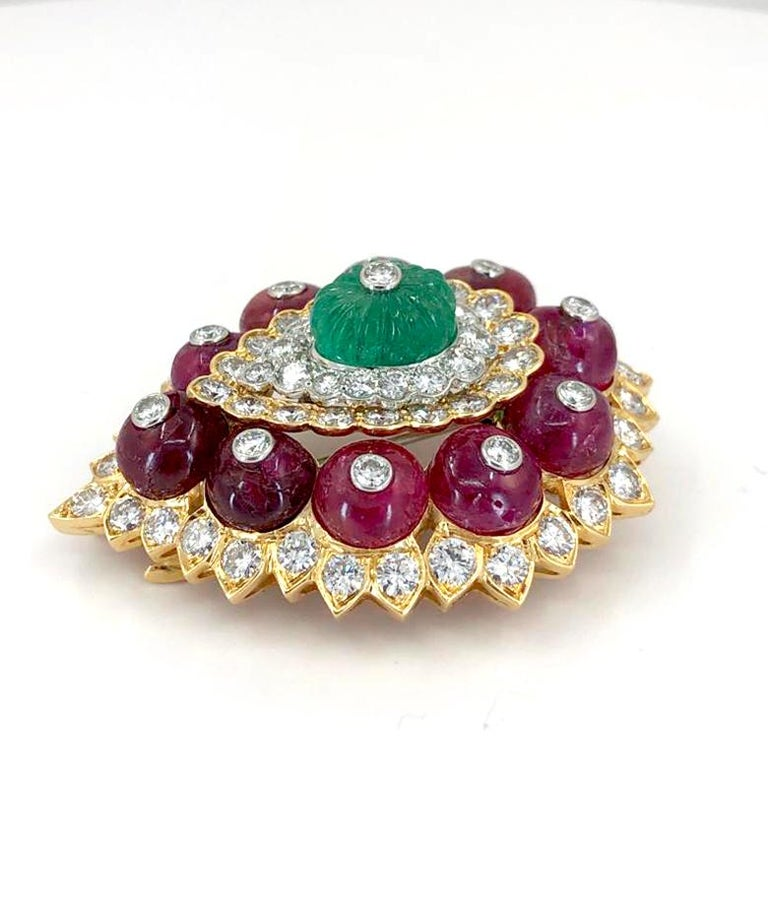 A sublime David Webb vintage brooch that dates back to the 1980s, centering a carved emerald surrounded with diamonds and rubies crafted in 18k yellow gold and platinum. The brooch measures approximately 2 1/4 inches in length and 1 3/4 inches in