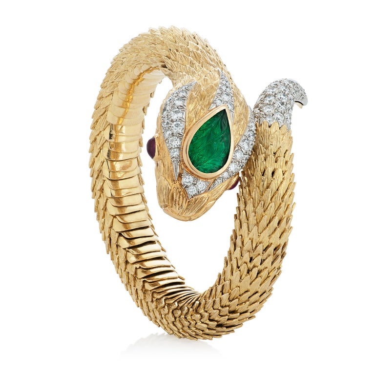 David Webb Snake Charmer bracelet accompanied by David Webb Certificate of Authenticity and original David Webb box.  This flexible snake bracelet features a 2.22 carat carved pear shape emerald and two oval cabochon ruby eyes totaling 1.10 carats