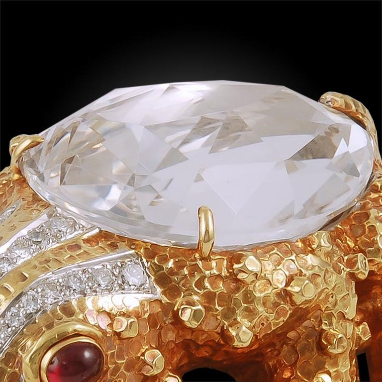 A textured 18k gold frog, set at the torso with a pear-shaped rock crystal, accented by round diamonds completed by two cabochon ruby eyes.  Signed David Webb.  Dimensions – 2″ x 2″; 69.6grams