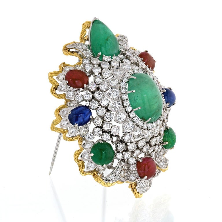 An impressive diamond and gemstone Heraldic Brooch from 1970's. Set with cabochon emeralds, rubies, and sapphires, brilliant-cut diamonds, 18K gold, and platinum. Length: 2.5 inches.
