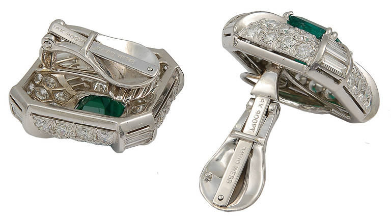A pair of 1980's emerald and diamond earclips by David Webb; each centrally set with a square vivid green Columbian emerald, with four rows of graduated baguette diamond columns, in a pave-set diamond mounting.  The earclips are mounted in platinum
