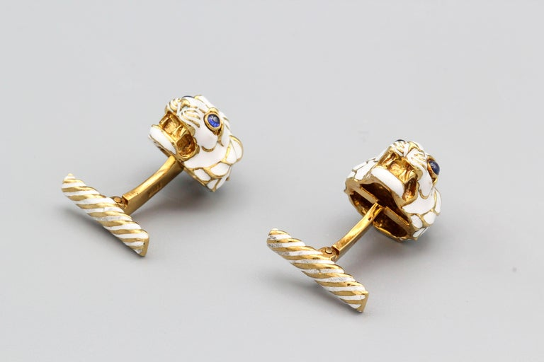 Fine pair of cabochon sapphire and 18K yellow gold cufflinks by David Webb. They resemble a lion's head, with cabochon sapphire as eyes and white enamel.  Hallmarks: Webb, copyright, 18K.